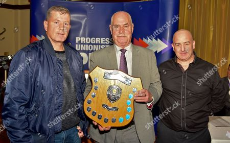 PUP's Ken Wilkinson (centre) presents the Billy Mitchell Award to members of the Seven Towers Community Association, Ballymena
