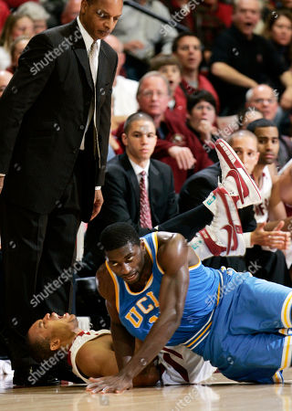 Lawrence Hill, Alfred Aboya, Tretn Johnson Stanford forward Lawrence Hill (15) and UCLA forward Alfred Aboya (12) fall as Stanford head coach Trent Johnson, upper left, watches in the second half of NCAA basketball action in Stanford, Calif