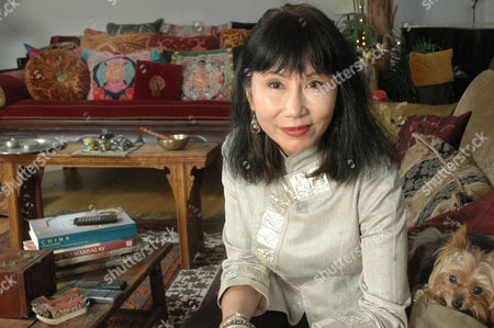 Author Amy Tan poses in her apartment in New York's Soho section, with her dog, Bubba