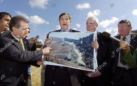 """PHOTO Rep. Duncan Hunter R-Calif., center left, holds up a photo showing the border area as Rep. Edward Royce, R-Calif., left, Rep. James Sensenbrenner, R-Wis., center right, and Rep. Randy Cunningham R-Calif., right, look on during a news confernce held in """"Smuggler's Gulch"""" along the U.S.-Mexico border in San Diego, . The news conference was held to urge the completion of a 14-mile-long section of fortified border fence in the area"""
