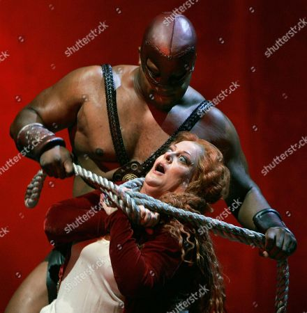 """Deborah Voigt, Marckarthur Johnson Soprano Deborah Voigt as Salome is killed by the executioner, played by Marckarthur Johnson, during dress rehearsal for the Lyric Opera of Chicago's production """"Salome"""" by Richard Strauss on"""