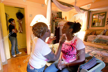Bride to be Lakeyma White, left, helps her sister, Kimberly White, both of Queens, with her make-up at the Saddle Down Bed and Breakfast as bride to be Keryn Hing talks on the telephone, in New York. After interviewing dozens of women who had children out of wedlock, Maryann Reid, author of the novel Mary Your Baby Daddy, decided to organize an event that would bring attention to the importance of two-parent households among black families. Ten selected couples with children were married during an all-expense-paid wedding, Thursday, made possible with donations by designers, wedding planners, caterers, make-up artists and officiated by the Rev. Herbert Daughtry of the House of Lord Church in Brooklyn