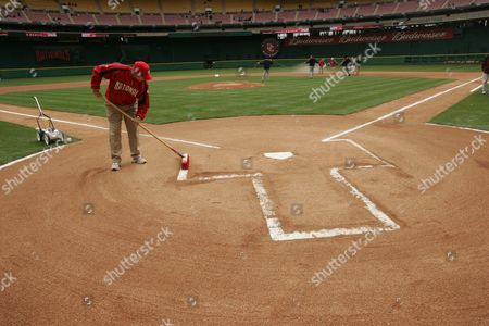 ROGERS Washington National groundscrew member Matt Rogers of Beltsville, Md.. readies the batter's box at RFK Stadium in Washington, before the start of the Nationals exhibition game against the New York Mets