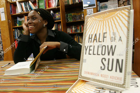 """Chimamanda Ngozi Adichie FILE- In this, Nigerian author Chimamanda Ngozi Adichie autographs copies of her novel, Half of a Yellow Sun, after a reading at Harvard Bookstore in Cambridge, Mass. Nigerian censors are effectively banning the film """"Half of a Yellow Sun"""" and will not even say why, the Nigerian-British producers told The Associated Press Thursday amid suspicions that censors fear it could rouse tribal rivalries. The National Film and Video Censor Board insisted it has not banned the movie but delayed its registration over """"some unresolved issues which have to be sorted out."""" The movie's Nigeria premiere was set for last Friday. Invitations had been sent out and the film was to play in every cinema in the country. On Thursday, the board told the distributors that the film had not yet passed the registration process. """"No the film hasn't been banned but we can't show it, which technically is a ban,"""" Biyi Bandele said in a telephone interview from his home in London, where the movie placed among the 10 most popular at cinemas over the Easter weekend. It stars Oscar nominee Chiwetel Ejiofor and Thandie Newton and is an adaptation of the book by prize-winning novelist Chimamanda Ngozi Adichie"""