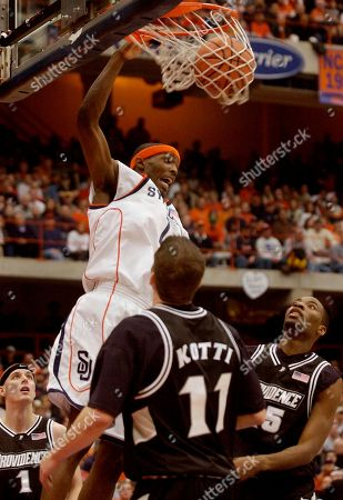 Stock Picture of WARRICK Syracuse's Hakim Warrick dunks for two of his game-high 36 points against Providence's Donnie McGrath (1), Tuukka Kotti, and Herbert Hill during the second half in Syracuse, N.Y., . syracuse won, 91-66