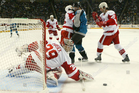Dominik Hasek, Steve Bernier, Kyle Quincey, Robert Lang Detroit Red Wings goalie Dominik Hasek, bottom, of the Czech Republic, stops a shot on goal as San Jose Sharks right wing Steve Bernier, center, collides with Detroit Red Wings' Kyle Quincey, left, and Robert Lang, of the Czech Republic, right, in the second period of Game 4 of a second-round NHL hockey playoff series in San Jose, Calif., . Detroit won 3-2 in overtime