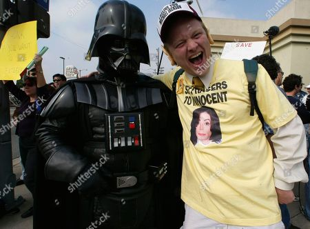 Jake Byrd from Chino, Calif., right, wearing a Michael Jackson t-shirt, jokes with a fan dressed as the film Star Wars' character Darth Vader, as they join about a hundred Star Trek fans upset by the cancellation of the shows latest series, Star Trek: Enterprise, at a rally, outside the Paramount Studios in Los Angeles. Paramount announced the cancellation jointly with UPN, which has seen ratings fall since its first episode in 2001. The show averaged 2.9 million viewers thisseason, compared with 5.9 million an episode in 2001. UPN plans to air the last program on May 13