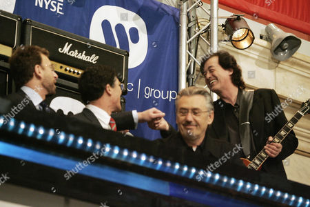 Led Zeppelin guitarist Jimmy Page, right, clasps hands with Warner Music Group Corp. Chairman & CEO Edgar Bronfman Jr., left, after Page played during New York Stock Exchange opening bell ceremonies, as part of Warner Music's IPO ceremonies. Also on the podium are NYSE CEO John Thain, second left, and Alan Callan, Page's business manager
