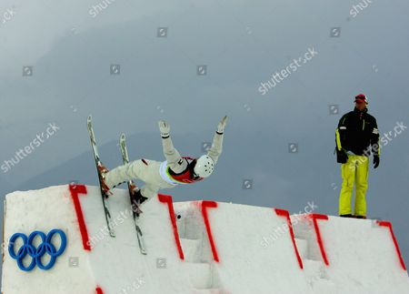 Jeret 'Speedy' Peterson of the United States jumps off the ramp as Switzerland's coach Michel Roth looks, during pratice ahead of Men's Aerials final, at the Turin 2006 Winter Olympic Games at Sauze d'Oulx, Italy