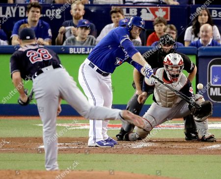 Toronto Blue Jays' Michael Saunders, right, hits a single off Cleveland Indians starting pitcher Corey Kluber during the second inning in Game 4 of baseball's American League Championship Series in Toronto
