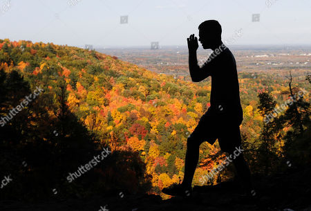 A hiker takes in the fall colors as he makes his way along the Indian Ladder Trail on a warm fall day at John Boyd Thacher State Park, in Voorheesville, N.Y