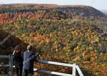 A couple takes in the view of fall colors at John Boyd Thacher State Park, in Voorheesville, N.Y
