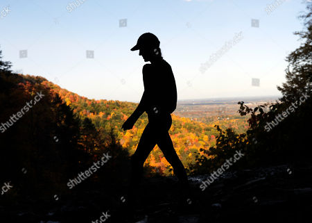 A hiker takes in the fall colors as she makes her way along the Indian Ladder Trail at John Boyd Thacher State Park, in Voorheesville, N.Y