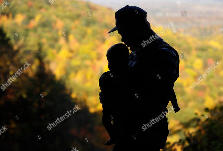 Christopher Valenzuela of Schenectady, N.Y., takes in the fall colors as he carries his sixth-month-old son Leonardo on the Indian Ladder Trail at John Boyd Thacher State Park, in Voorheesville, N.Y