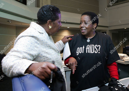 ESCOTT HALL Rep. Laura Hall, right, D-Huntsville, gives a ''Got AIDS?' T-Shirt to her colleague, Sen. Sundra Escott, D-Birmingham, on the floor of the state Senate, at the Alabama Statehouse, in Montgomery, Ala. Hall, chairwoman of the House Black Caucus, said she hopes the T-Shirts will cause legislators to go home and get tested for HIV infection. She said if lawmakers were tested it would encourage their constituents to find out if they have AIDS