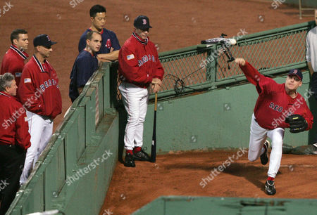 Boston Red Sox's Curt Schilling, right, throws in the bullpen at Boston's Fenway Park before Game 3 of the ALCS with the New York Yankees, . Watching are Dr. William Morgan, left; general manager Theo Epstein; second left; manager Terry Francona, third left; and coach Dave Wallace, center. Schilling was scratched from his scheduled Game 5 start in the ALCS because of a sore ankle and will be replaced by Derek Lowe