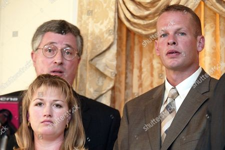 Stock Photo of ADKINS Sgt. Jason Adkins, right, is flanked by his wife, Amy, and his attorney Thomas S. Neuberger, as he faces reporters, in Wilmington, Del. Adkins filed a civil rights lawsuit against Secretary of Defense Donald Rumsfeld; Air Force Secretary James Roche; General John Handy of the Air Mobility Command, and Dover base commander Col. John Pray Jr