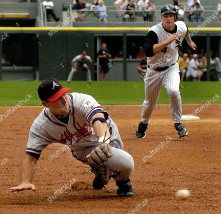 CREDE DEROSA Atlanta Braves third baseman Mark DeRosa, left, dives but is unable to grab a ball hit by the Chicago White Sox' Juan Uribe as the White Sox's Joe Crede, right, takes off from second during the fourth inning, in Chicago. Crede scored on the play