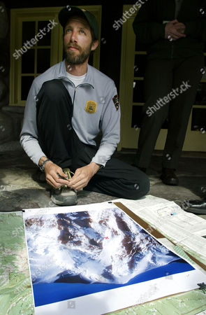 GOTTLIEB, COOLEY, RICHARDS David Gottlieb, a climbing ranger at Mt. Rainier National Park sits next to a photo of Mt. Rainier as he talks to reporters, in Longmire, Wash. Gottlieb spoke about the rescue of mountain climbers Scott Richards and David Cooley who became stranded Saturday after Cooley, who died en route to medical care after being plucked from the mountain by helicopter Monday evening, fell and suffered a head wound. Gottlieb was one of two rangers who climbed up the moutain to reach Richards and Cooley before the helicopter rescue of Cooley could be accomplished. Richards was rescued by helicopter on Tuesday
