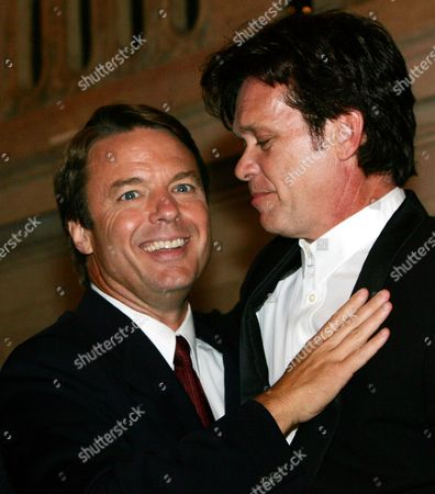 Sen. John Edwards, D-N.C., left, greets musician John Cougar Mellencamp at a party at the Wang Theater in Boston, on . Edwards had just completed his address to the 2004 Democratic National Convention
