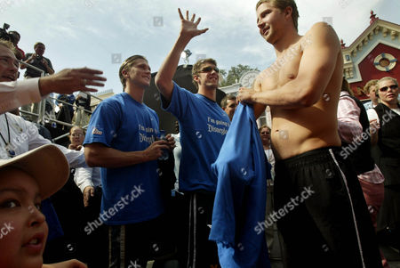 Stock Image of PHELPS CROCKER KRAYZELBURG Olympic swimmers Michael Phelps, center, Ian Crocker, right, and Lenny Krayzelburg prepare to leave a Disneyland event honoring them, in Anaheim, Calif. A swim team from Southern California, comprised of youngsters from 5 to 15-years-old, welcomed and cheered on the Olympians and even participated in a relay and match race with the three athletes