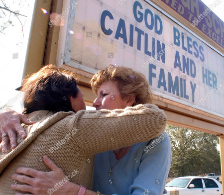 Stock Photo of TEACH JONES Dana Jones, right, a counselor at the Bell High School in Bell, Fla., is hugged by a teacher, outside the school by a sign which was put up after the death of Caitlin Huggins, who died of cancer after a long illness. Caitlin, with the help of Dana Jones, was given her wish to graduate from high school before she died. Caitlin graduated last September