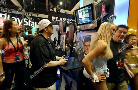 "ADAN FUSON MICHELLE-HILL Jay Adan, second from left, plays ""Playboy - The Mansion,"" the video game, while playboy bunnies Stacy Fuson, third from right, and Lauren Michelle-Hill, right, pose with a visitor at the Electronic Entertainment Exposition (E3), in Los Angeles. E3 is the world's leading interactive entertainment trade event"