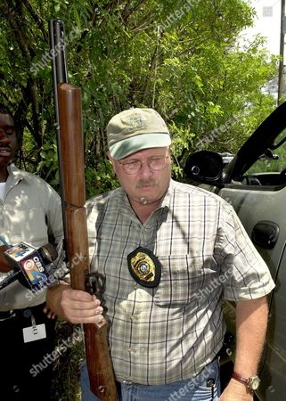 Stock Photo of DENNIS Lt. Charles Dennis of the Florida Fish and Wildlife Commision shows a tranquilizer dart rifle that the agency hopes to use to subdue an escaped tiger, in Loxahatchee, Fla. A 600-pound tiger continued to elude capture Tuesday after escaping from the compound of its owner, a former actor who once played Tarzan