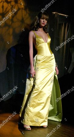 A model wears a goldenrod silk satin corseted ballgown at the Bradley Bayou for Halston Spring 2005 collection, in New York