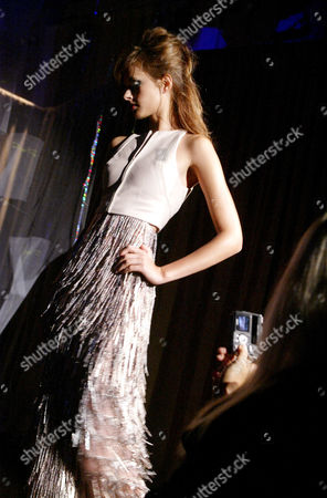 A model wears a pink lambskin vest with a metallic embroidered high waisted skirt at the Bradley Bayou for Halston Spring 2005 collection, in New York