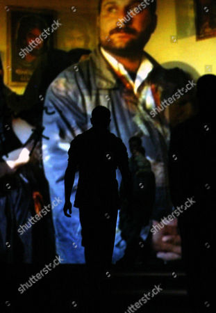 Stock Photo of A projected photogragh by Lynsey Addario from her coverage of Iraq, silhouettes a model during the Imitation of Christ Spring 2005 fashion show from designer Tara Subkoff at the Bryant Park tents in New York