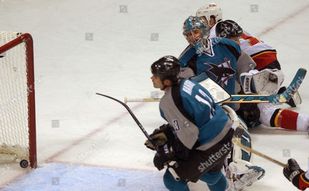 Stock Image of DONOVAN San Jose Sharks right wing Todd Harvey, lower, Sharks goalie Evgeni Nabokov, center, from Kazakhstan, and Calgary Flames right wing Shean Donovan, upper right, watch the puck go into the net from Flames defenseman Steve Montador, not shown, for the winning goal in overtime to beat the Sharks, 4-3, in Game 1 of the NHL Western Conference final series in San Jose, Calif