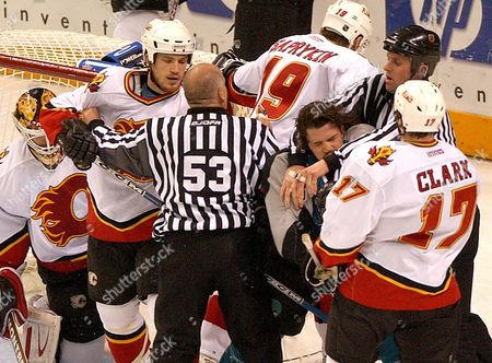 San Jose Sharks' Todd Harvey is restrained by referees from an altercation with the Calgary Flames in the second period of Game 2 of the NHL Western Conference final series in San Jose, Calif., . Calgary won the game, 4-1