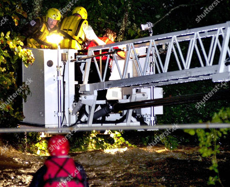 RADFORD CALLAWAY RION Asheville firefighters Ken Radford, left, and Tim Callaway, center,help, Kathrine Rion, right into the bucket of a ladder truck after rescueing her from a group of trees in the middle of the Swananoa River in Black Mountain, N.C., late, after the car she was driving was washed off a bridge by floodwaters