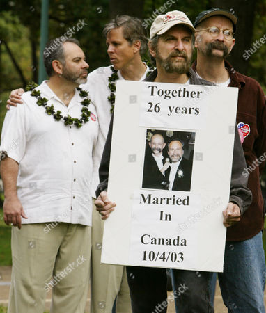 Stock Photo of VOORHEIS Couples that are supporters of same-sex marriage, from left, Ron Lussier and Dan Greening of Bellingham, Mass., and Michael Sabatino and Robert Voorheis of Yonkers, N.Y., listen to speeches during a stop in the Marriage Equality Caravan 2004 tour on Capitol Hill in Washington . With the U.S. Capitol at their backs, supporters of gay marriage pleaded, demanded and sang out for equal rights Monday, capping an 11-city bus tour