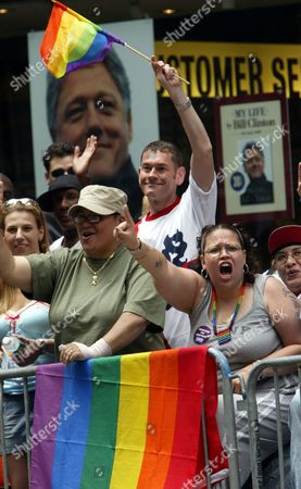 Elizabeth Ortiz, left, and Marisol Burgos, right, both from Brooklyn, and Peter Cleary, background, of London, cheer on the participants of the New York's Lesbian, Gay, Bisexual and Transgender Pride March as they march down Fifth Ave, . The parade commemorated the Stonewall uprising of 1969, when gay bar patrons resisted a police raid