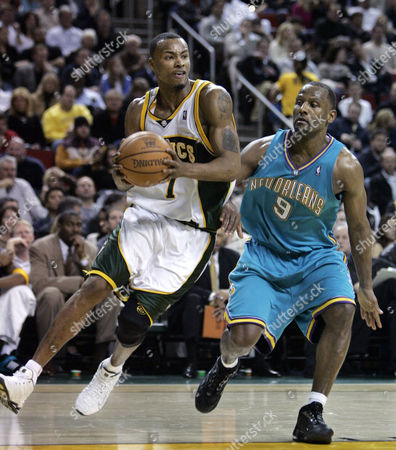 LEWIS LYNCH Seattle SuperSonics' Rashard Lewis, left, drives against New Orleans Hornets' George Lynch in the third quarter, in Seattle. The Sonics won, 108-91