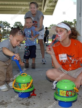 HALL FOSS Student Volunteers Stacie Foss, right, and Jenny Hall, standing background, blow bubbles with children at the Vineland Elementary School Tuesday morning in Englewood, Fla. Volunteers try and keep children, who along with their families, were displaced by Hurricane Charlie, busy during the day with activities. The L.A. Ainger Middle School has set up a Red Cross Shelter