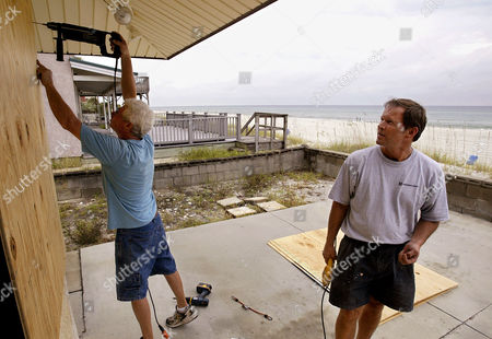 PANAMA CITY HURRICANE Jack Short, right, checks his work as friend Perry Ashe screws a piece of plywood into place as Ashe helps Shout board up his mother, Sue Ward's, house on the beach in Panama City, FL., Monday morning . Hurricane Ivan is predicted to make landfall somewhere on the western panhandle of Florida later this week