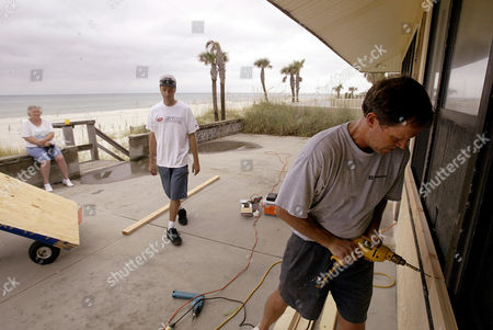 IVAN Jack Short, right, screws a piece of plywood into place as his mother, Sue Ward, sitting on wall, watches him board up her house on the beach in Panama City, FL., Monday morning . Short's step-son John McGarity, center, walks over to lend a hand. Hurricane Ivan is predicted to make landfall somewhere on the western panhandle of Florida later this week