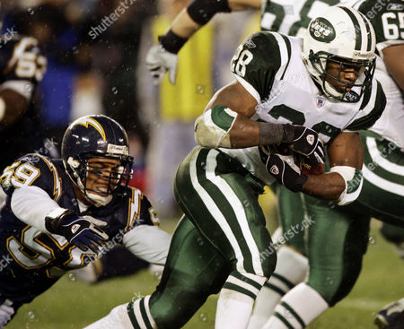 New York Jets runningback Curtis Martin (28) rushes for a gain as he evades the grasp of San Diego Chargers linebacker Donnie Edwards (59) during the first quarter of the AFC wild-card game in San Diego