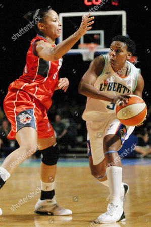 Stock Image of New York Liberty's Crystal Robinson looks to pass the ball against pressure from Charlotte Sting's Allison Feaster during the second half at New York's Radio City Music Hall . Robinson was the game's high scorer with 16 points in the Liberty's 56-52 victory over the Sting