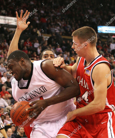 MAXIELL SCHENKE University of Cincinnati's Jason Maxiell pulls down a rebound as Miami (of Ohio) Universitys' Tim Schenke tries to stop him in the first half in Cincinnati . The Miami player behind is unidentified