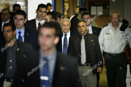 Israeli Prime Minister Ariel Sharon, center, is escorted by bodyguards as he arrives for a Foreign Affairs and Defense committee meeting in the Knesset, Israel's parliament, in Jerusalem . At right is Sharon's military secretary Yoav Galant