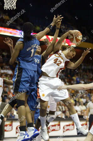 SALES HOLSCLAW MELVIN Connecticut Sun's Nykesha Sales, right, pulls down a rebound over the defense of the Washington Mystic's Chamique Holdsclaw (1) and Chasity Melvin, center, in the first half of the game in Uncasville, Conn., . The Sun won 75-65