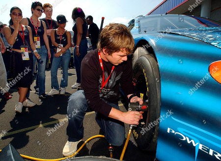 "HUDSON Jon Peter Lewis, right, a finalist on the show ""American Idol"" tries to change a tire on a race car as other finalists, from left, Jasmine Trias, Amy Adams, John Stevens, Camile Velasco, and Jennifer Hudson look on before the start of the Coca-Cola 600 race at Lowe's Motor Speedway in Concord, N.C"