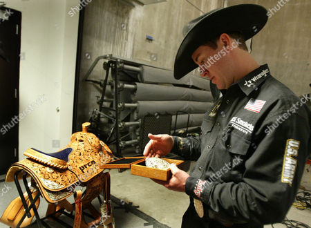BRAZILE Three-time all-around world champion Trevor Brazile of Decatur, Texas cowboy checks out his gold belt buckle and his saddle at the Thomas & Mack Center in Las Vegas after the final go-round of the National Finals Rodeo