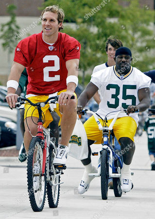 COUCH BRIGGS Green Bay Packers quarterback Tim Couch (2) and fullback Kris Briggs ride bicycles to training camp, in Green Bay, Wis. Friday was the first day of camp for rookies and first-year players