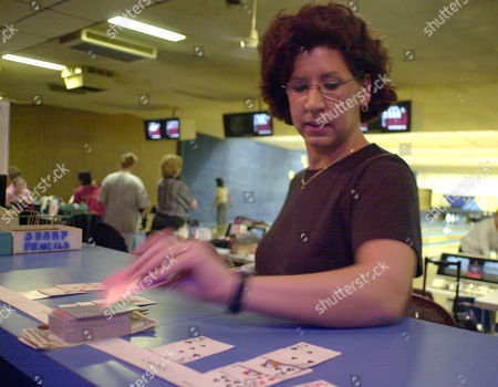 JOHNSON Liz Johnson of Cheektowaga, N.Y., pulls a card from the deck after making a strike in league-play at the Ideal Bowling Center in Buffalo, N.Y. on . The more strikes in a game offer better possibilities of a winning poker-hand in the league-play community spirit game