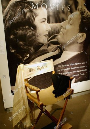 """Katharine Hepburn's movie set chair with a gold plate on the right arm engraved with """"Miss Hepburn,"""" is on display at Sotheby's in New York, . In the background is a photo of Hepburn and Spencer Tracy from their first movie together, the 1941 film """"Woman of the Year."""" Property from Hepburn's estate will be auctioned on June 10 & 11, 2004"""